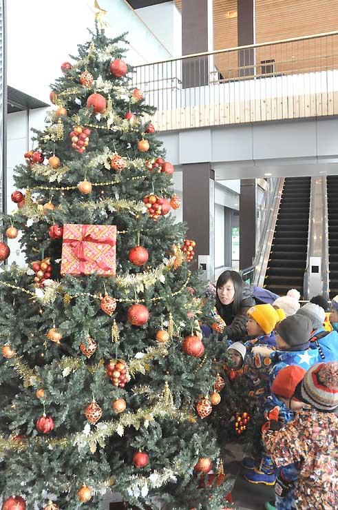 JR飯山駅構内のクリスマスツリーを眺めるあきは保育園の園児たち