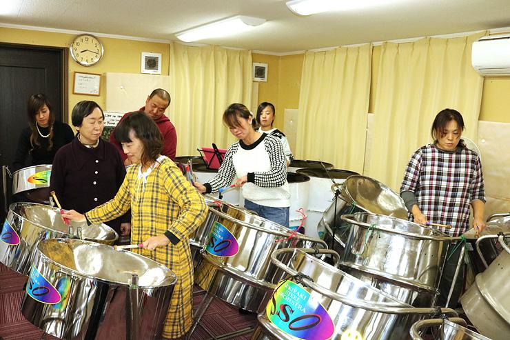 岡田さん(左から2人目)の前で演奏する「スキヤキ・スティール・オーケストラ」=南砺市広安