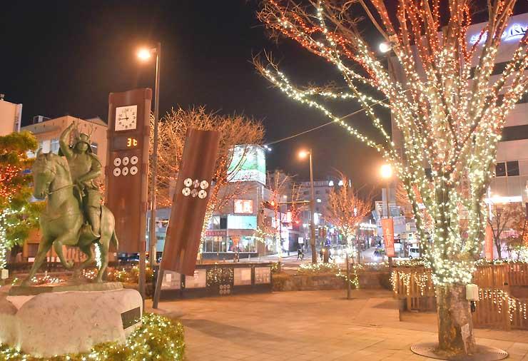 イルミネーションが点灯し、真田幸村像(左)を照らす上田駅前お城口広場