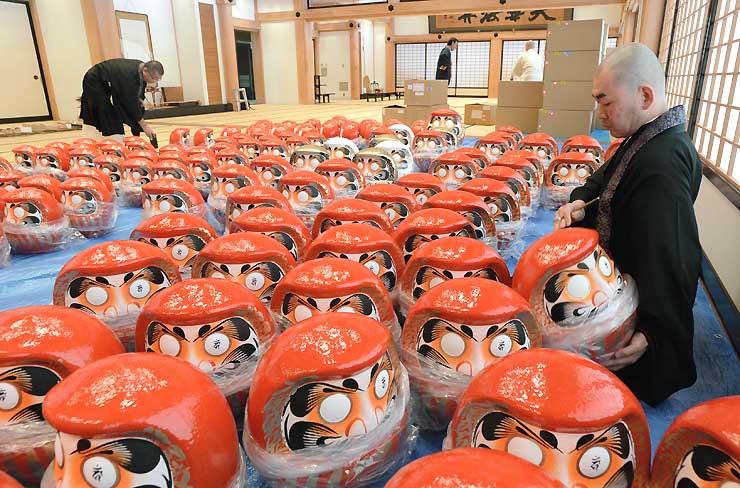 だるまの左目に梵字を書き入れる僧侶たち=21日、長野市の善光寺大勧進