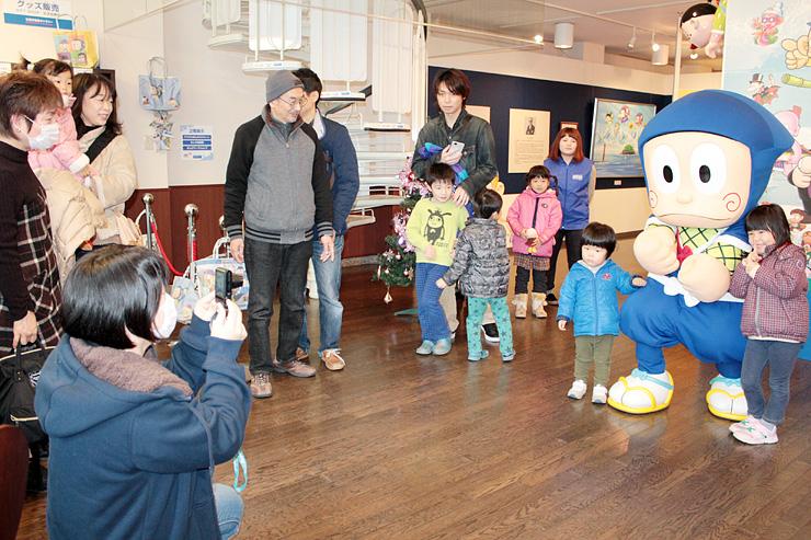 「忍者ハットリくん」の着ぐるみと記念撮影を楽しむ子どもたち=氷見市潮風ギャラリー