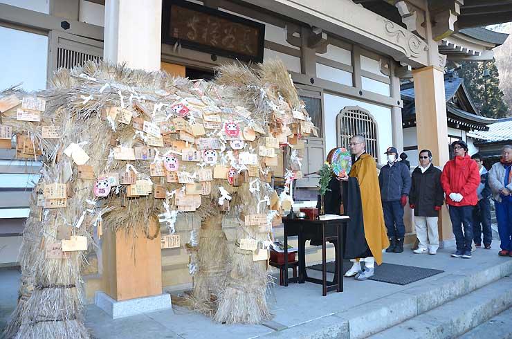 「大わら馬」に結び付けられた多くの絵馬と、祈願成就のため経を上げる宮下副住職