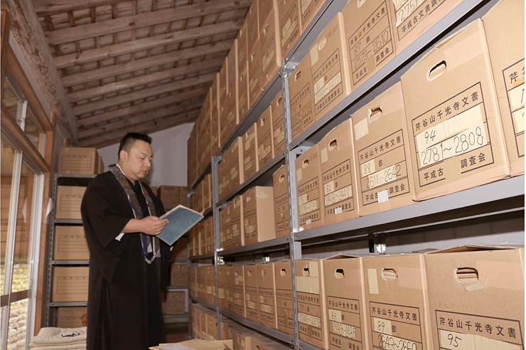 蔵書が整理された段ボール箱から古書を確認する安念住職