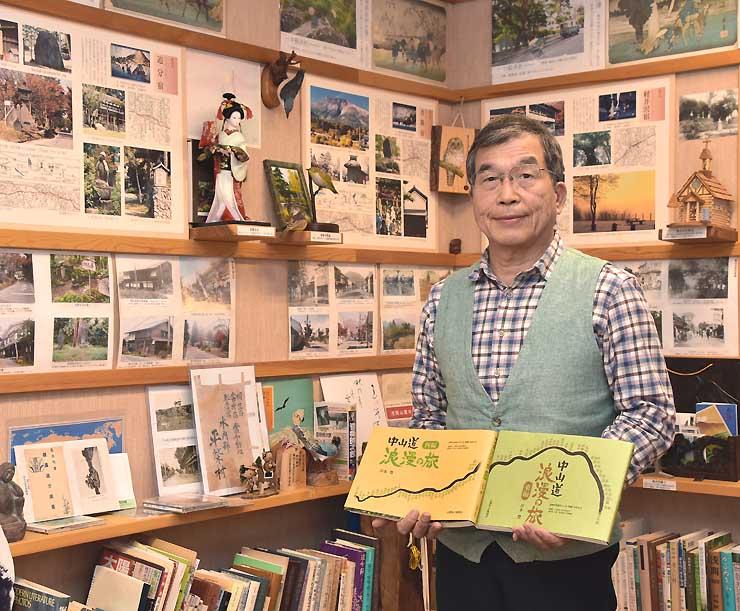 中山道69次資料館で、全面改訂した「中山道浪漫の旅」東編と西編を手にする岸本さん