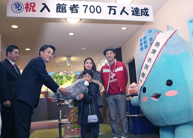 村椿市長(左から2人目)から記念品を受け取る池田さん(同3人目)