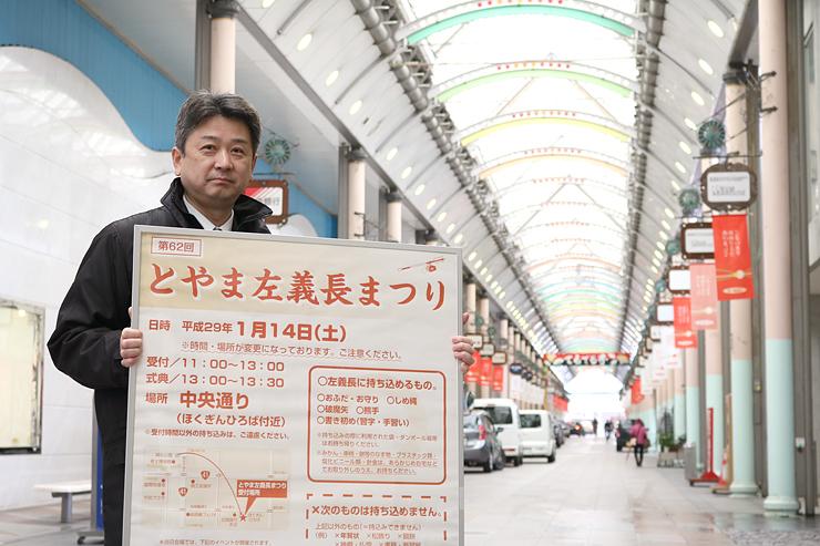 とやま左義長まつりが開かれる中央通りでポスターを手にPRする富山商議所職員