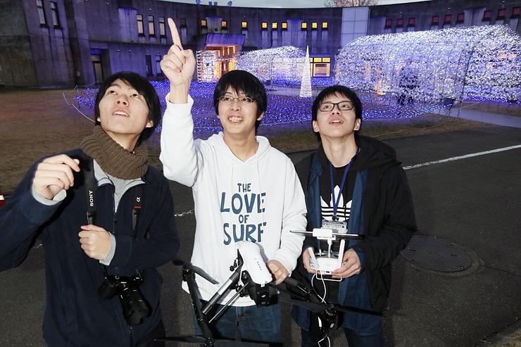 「おやべイルミ」の会場でドローンを手に打ち合わせる(左から)高松さん、森さん、安久さん=クロスランドおやべ