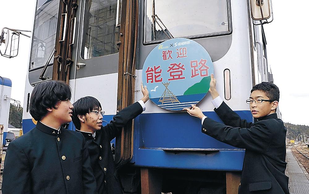 自らデザインしたヘッドマークを列車に取り付ける生徒=のと鉄道穴水駅