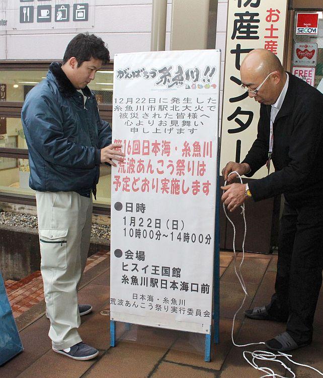 「糸魚川荒波あんこう祭り」の看板を取り付ける関係者=5日、糸魚川市