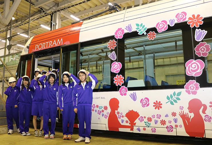 自分たちでデザインしたラッピング車両の前で、笑顔で写真に納まる生徒=富山ライトレール車両基地