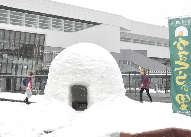 かまくら応援隊がJR飯山駅前に造ったかまくらで遊ぶ観光客ら=13日