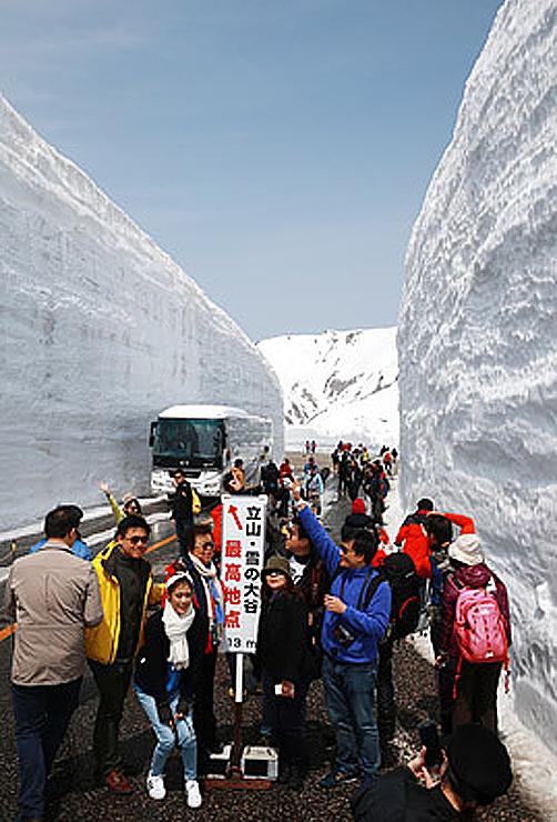 高さ13メートルの雪壁がそそり立つ「雪の大谷」を散策する大勢の観光客=2016年4月16日、立山・室堂