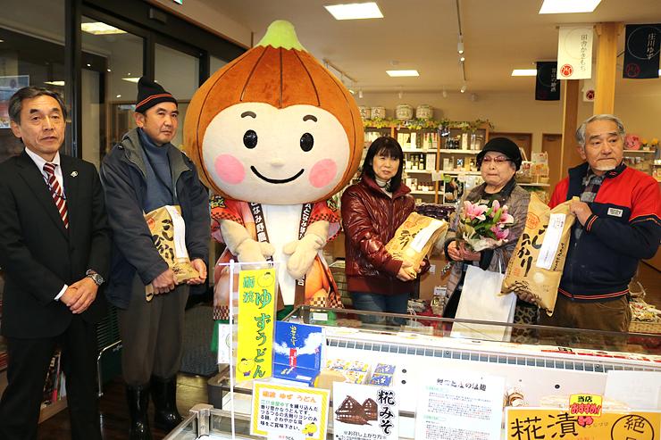 林常務理事(左)から記念品を受け取った黒田さん(右から2人目)ら来場者と篠島会長(右)