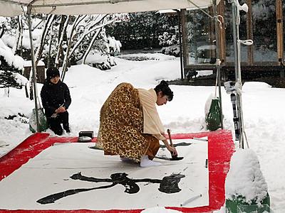 雪の日本庭園で書を披露 青柳志郎三代展