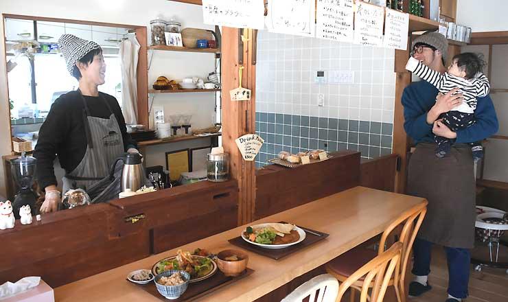 食堂の営業を始めた埋橋幸希さん(左)と長男を抱っこする智徳さん