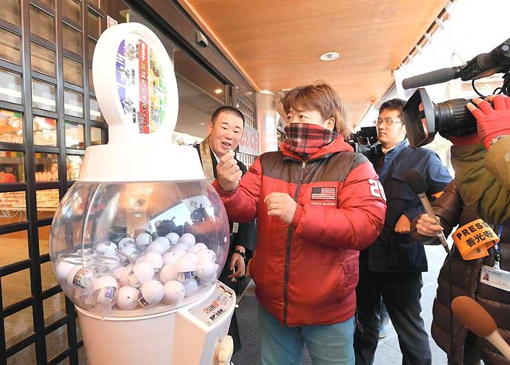 設置されたばかりのカプセル玩具販売機で、早速運試しをする参拝客
