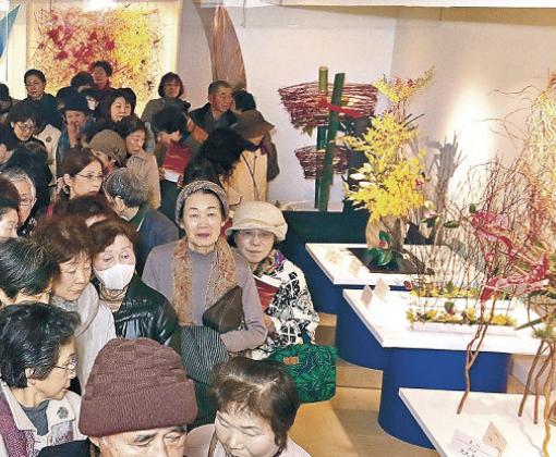 装いを新たにした会場で、県華道界をリードする作家の作品を鑑賞する愛好者=金沢市のめいてつ・エムザ8階催事場