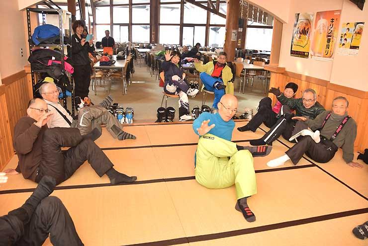 ゲレンデにあるレストランの一角で開かれたストレッチの講座。滑りを楽しむシニア世代が立ち寄り、講師から指導を受けていた=18日