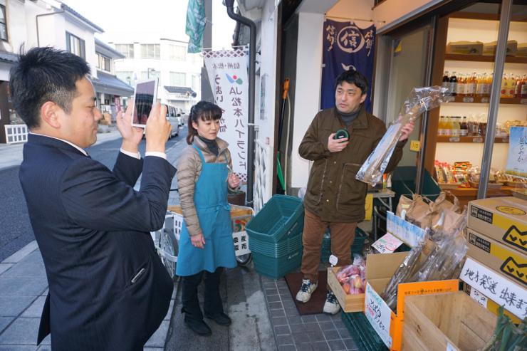 ネット中継で地元産のナガイモを紹介する松木さん(右)