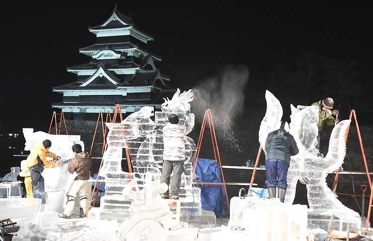 夜を徹して制作するコンクールの参加者=22日午前1時すぎ、松本市の松本城公園