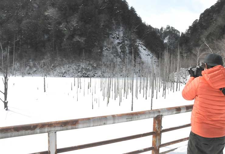 結氷した自然湖を撮影する山岸さん