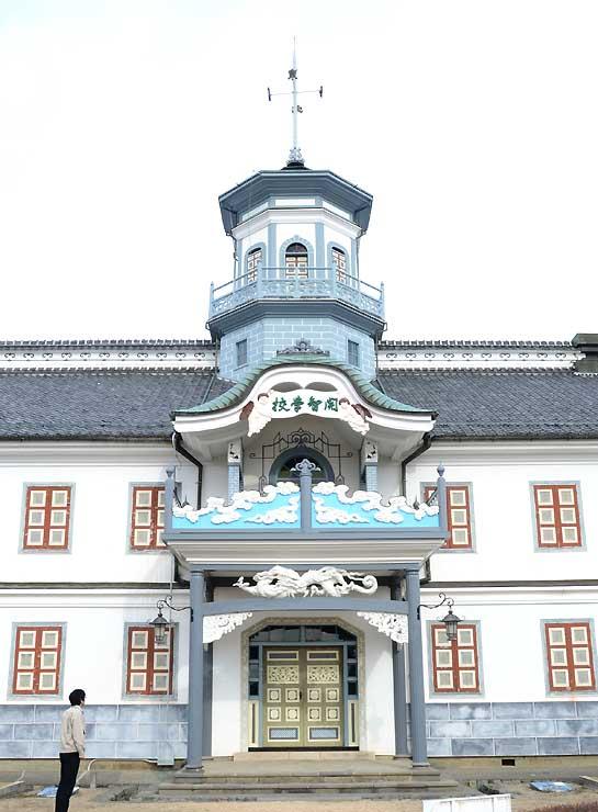 八角塔や車寄せ部分が塗装し直された旧開智学校校舎=24日、松本市