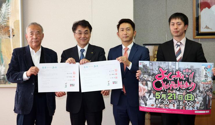 協定書やポスターを披露する(左から)松田会長、村椿市長、高下委員長、「よっしゃ来い!!」の高森広報部会長