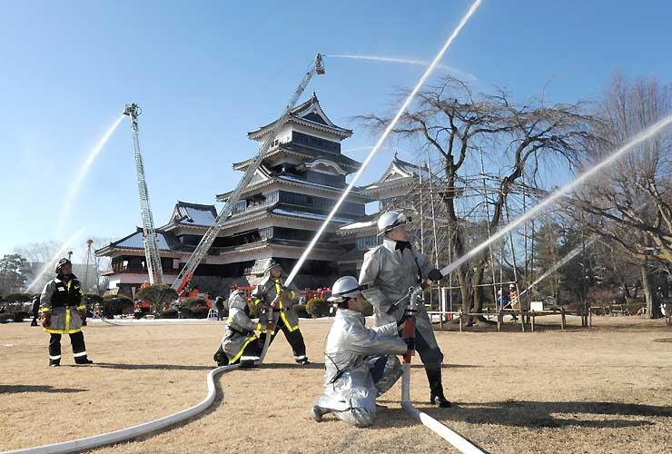 松本城の本丸庭園で一斉に放水する消防隊員ら=26日、松本市