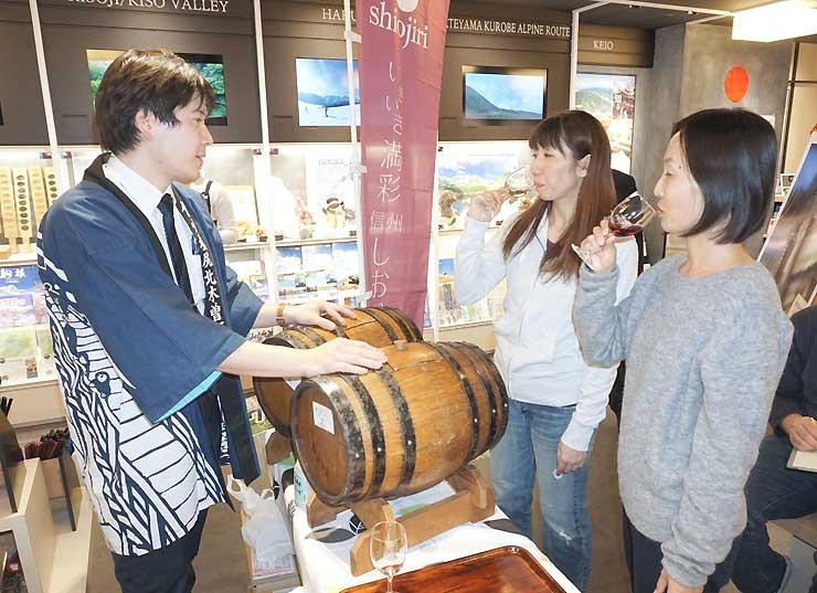 新宿駅地下街の観光案内所で、塩尻産ワインを試飲する人たち=27日、東京・新宿区