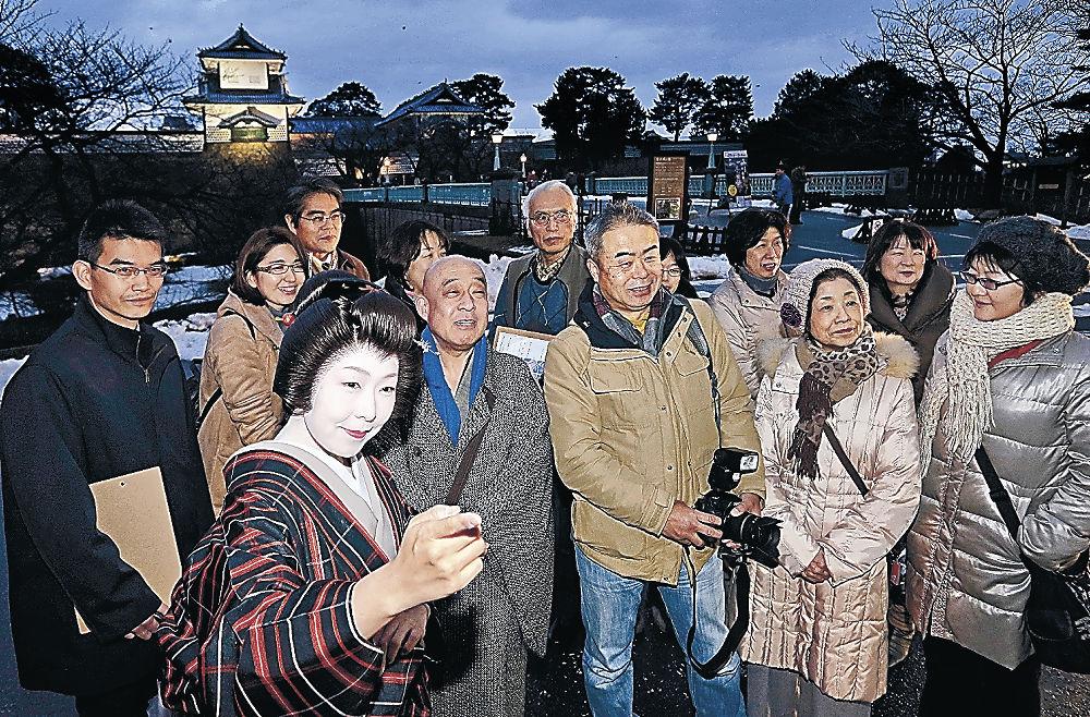 芸妓の純子さん(手前左)の案内で観光を楽しむ参加者=金沢城石川門前