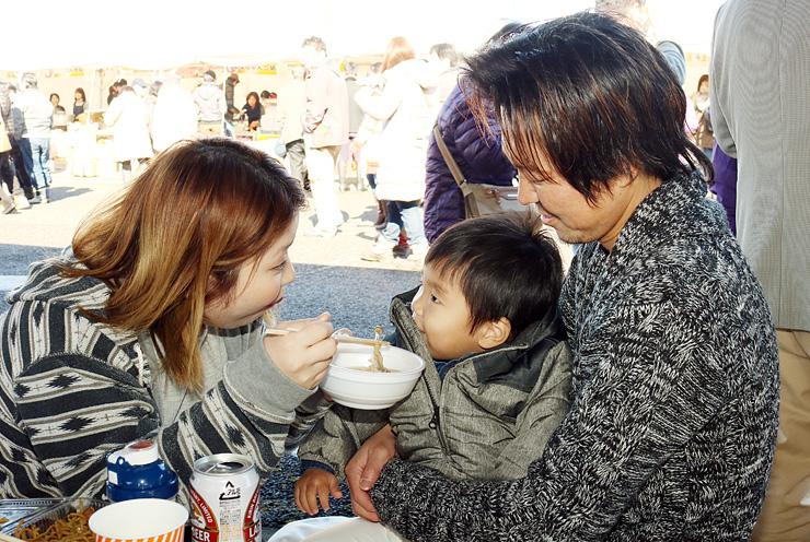 お母さんに鍋を食べさせてもらう子ども=グリーンパーク吉峰