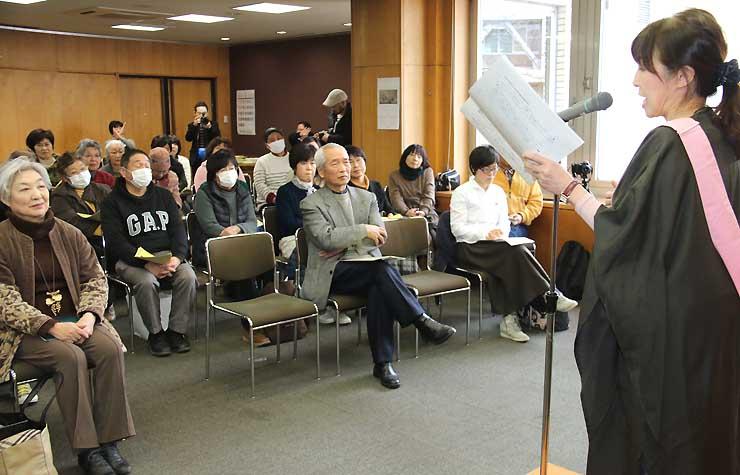 青木さん(手前右)の朗読に聞き入る参加者たち