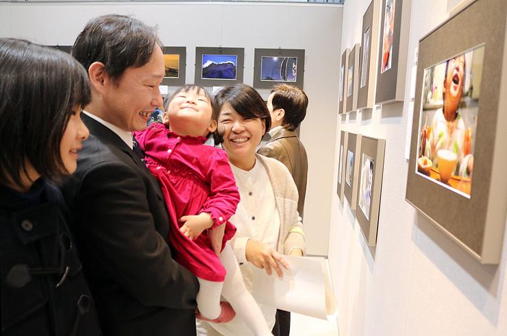 大賞作品「smile」(右)のモデルとなった初禾ちゃんを抱き家族と作品を眺める若原さん(左から2人目)=ミュゼふくおかカメラ館