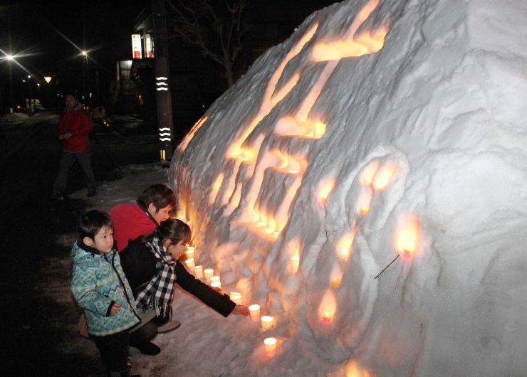 「結」と彫られた雪壁の周囲にろうそくを並べる参加者=28日、魚沼市小出島