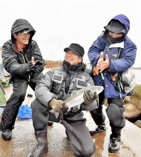 解禁初日に釣り上げたサクラマスを手に笑顔を見せる釣り人=1日、福井市六日市町の九頭竜川