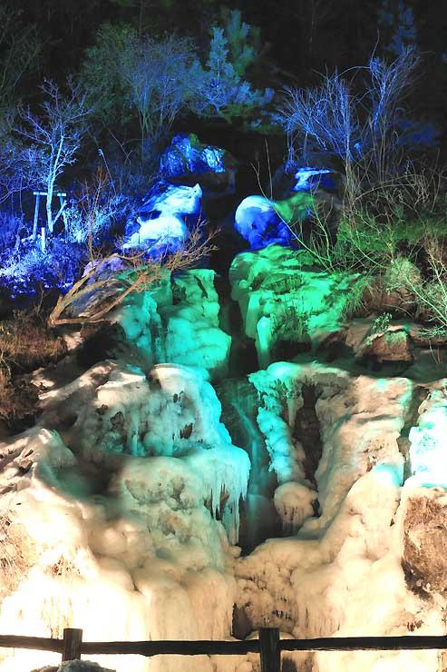 大部分が凍り、3色のライトに浮かび上がる滝=飯田市千代