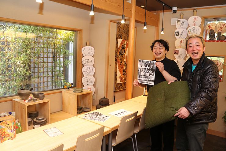 和風カフェ次元で座布団を手に寄席をPRするだら~ず山下さん(右)とチラシを手にする長徳社長