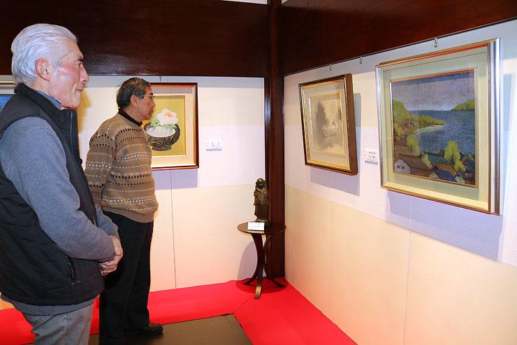 浅井省己さんが収集した展示作品を見つめる浅井克躬さん(左)ら=世界一かわいい美術館