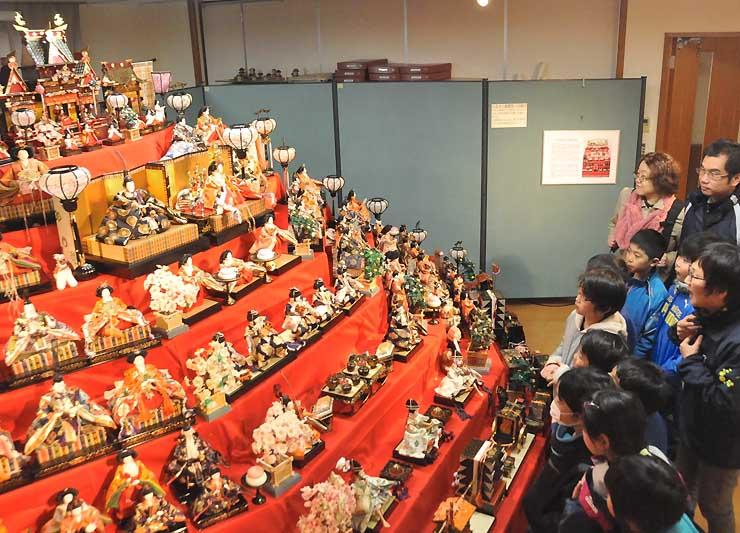 市民から寄せられたひな人形で作った「扇形八段飾り」を眺める飯山市東小学校2年生たち