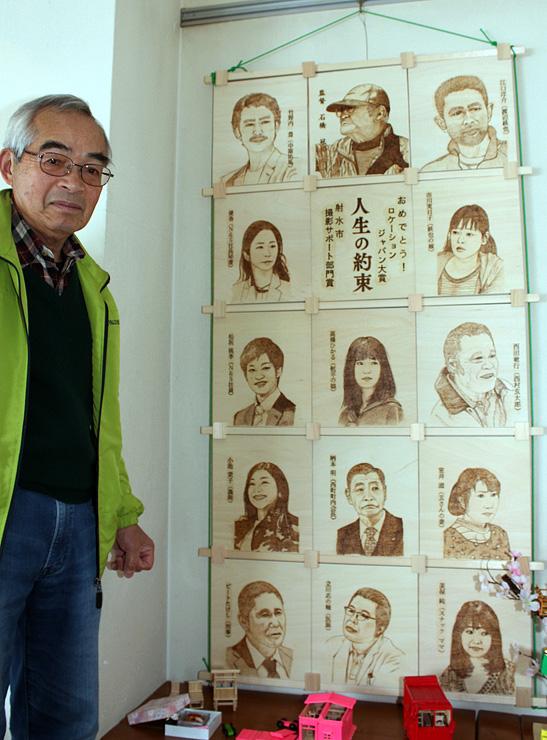 映画「人生の約束」の監督と俳優陣を焦がし絵で描いたパネル作品を展示する若松さん=ニューモンブラン