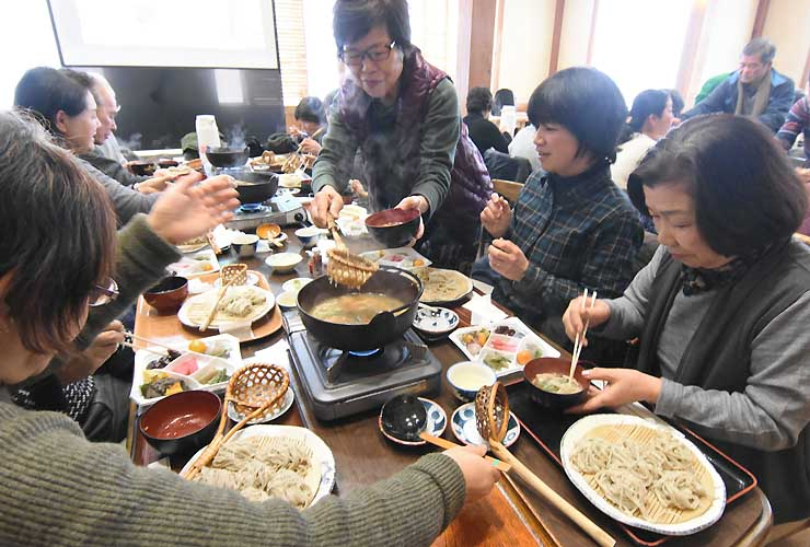 松本市奈川地区の郷土料理「とうじそば」を味わう観光客ら