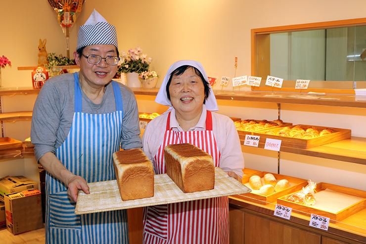食パンを手に笑顔を見せる宮腰さん(左)と妻の恵美子さん