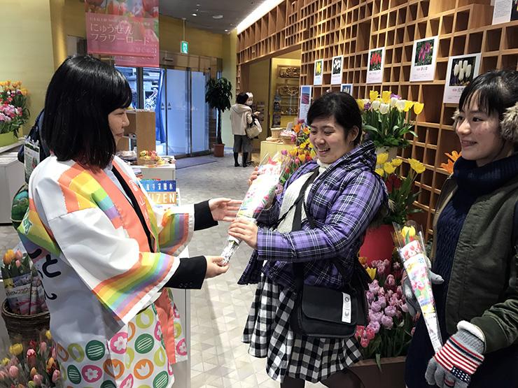日本橋とやま館でチューリップの切り花を配る職員(左)