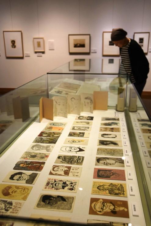 展示している「榛の会」の年賀状。会の20回を記念した作家たち自画像の版画も並ぶ