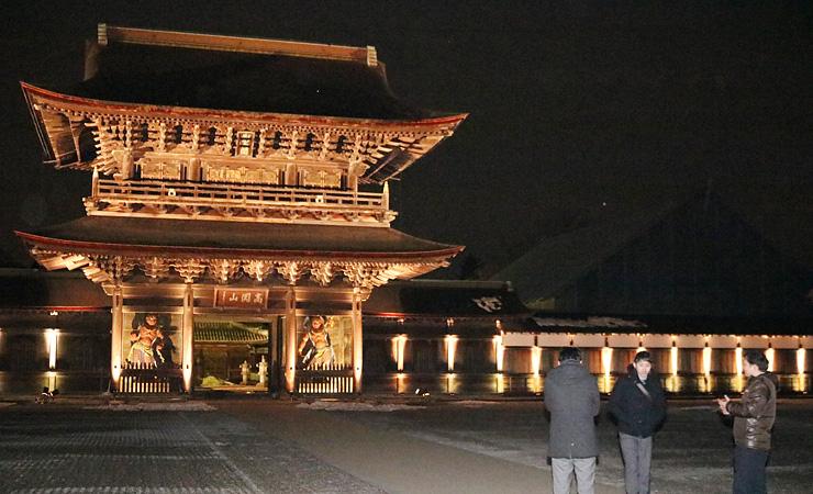 試験点灯で闇に照らし出された山門と回廊=瑞龍寺