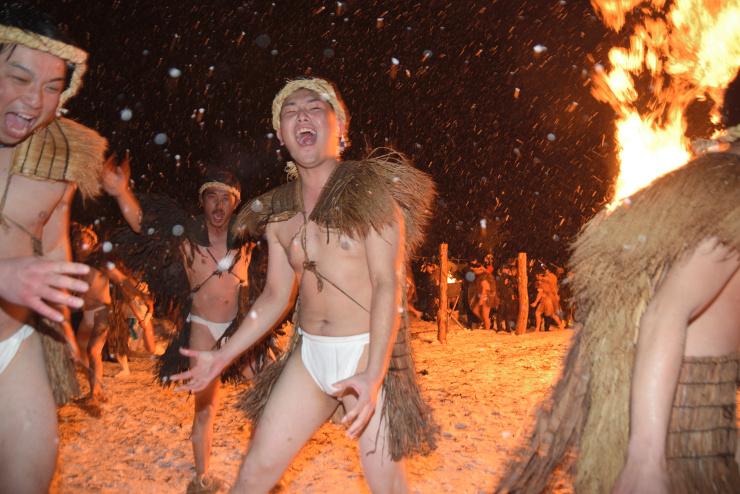 激しく降る雪の中を大声を上げて走り回る鬼役の男性たち