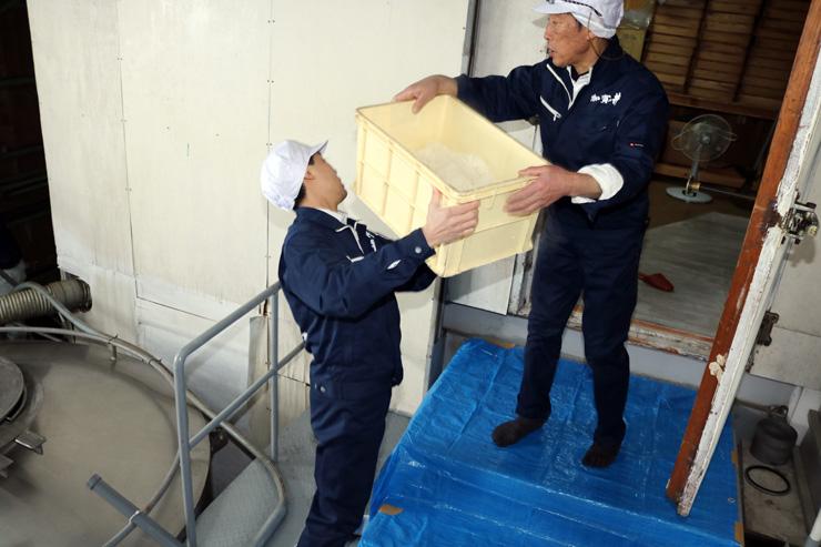 蒸した酒米をこうじ室に運び込む加賀の井酒造の関係者=銀盤酒造