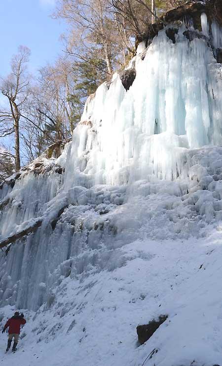 差し込んだ日光に青白く輝く湯川渓谷の氷壁=14日午前10時すぎ、南牧村