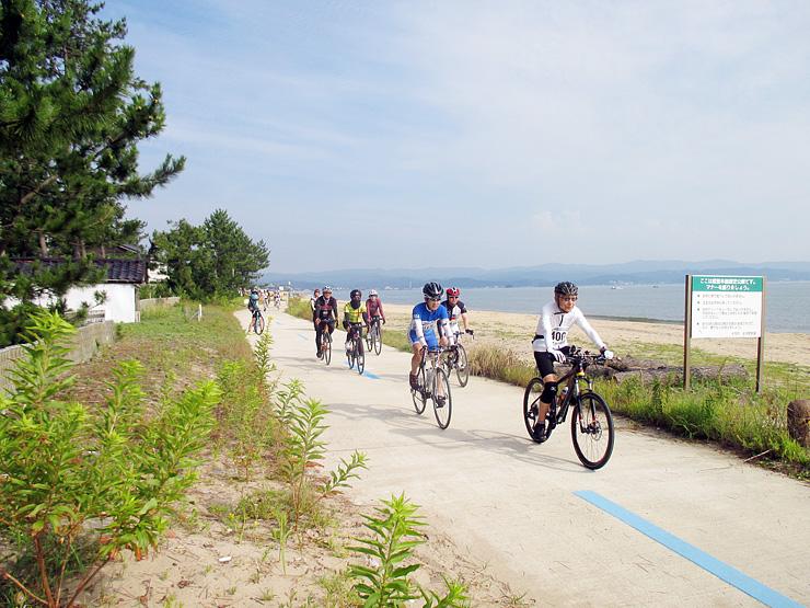 昨年7月に開催された「富山湾岸サイクリング2016」で自転車専用道を走る参加者=氷見市島尾