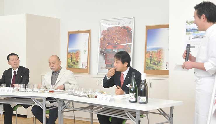 試食する玉村さん(左から2人目)らに料理を説明する関さん(右)